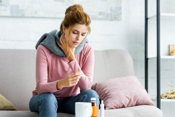 Kobieta z infekcją gardła, mierząca temperaturę