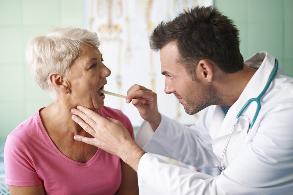 Sprawdzenie przez lekarza, czy występuje kandydoza jamy ustnej u pacjenta